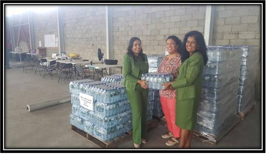 Ms. Elena Villafana-Sylvester (CEO, F.E.E.L Organization) happily accepts 300 cases of water for our Caribbean neighbours from SAPH Representatives